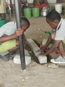 Några av barnen lär sig hur man bygger hus.